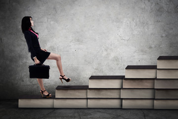 Businesswoman walking on the books stair