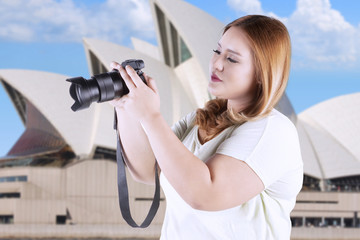 Fat woman takes picture at opera house