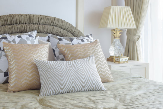 Graphic pattern silver and golden pillows setting on bed with light gold color blanket in classic style bedroom