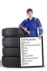 Mechanic standing with board and tyres