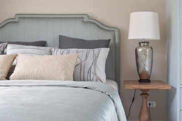 Romantic style bedding with satin blanket and reading lamp on wooden bedside table