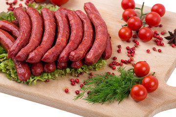 Smoked sausages on a kitchen wooden board on white background