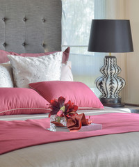 red bed and pillows with plant in glass vase on tray in bedroom
