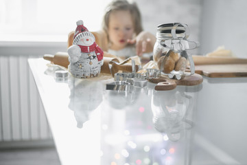 Emotional little girl in anticipation of Christmas baking gingerbread house near the window