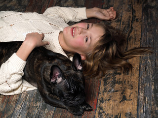 Happy girl and dog embracing lying on an old wooden floor