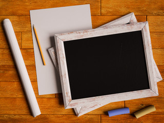 Chalkboard and colorful chalks over wooden table. 3D illustration