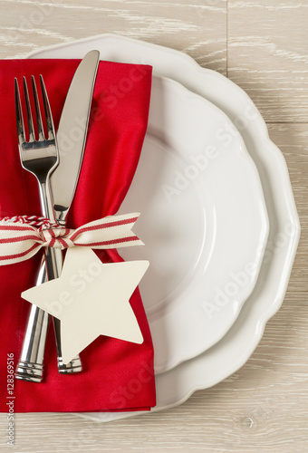 Festive Christmas Table Setting Place With White China Plates Red Cloth Napkin And Silverware