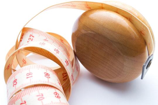 Yo-yo effect concept. Wooden yoyo with centimeter measure.