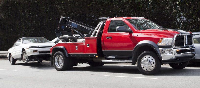 Surprise! Your car is G-O-N-E! Red tow truck hauling away white car. Horizontal.