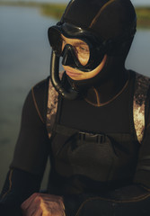 Man in wetsuit wearing goggles and snorkel