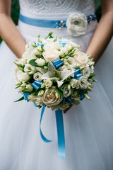 Cropped image. The bride holds a wedding bouquet of white roses and blue satin ribbons