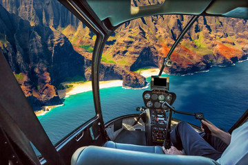 Helicopter cockpit flies in Na Pali coast, Kauai, Hawaii, United States, with pilot arm and control board inside the cabin. Wall mural