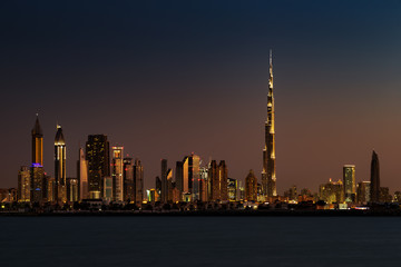 A skyline view of Dubai at Sunset from Jumeirah Beach. It showcases the buildings of Sheikh Zayed Road and Burj Khalifa
