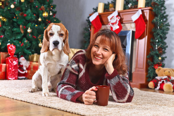 woman with dog in the room with Christmas decorations