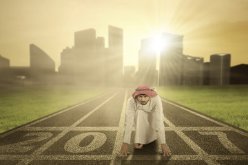 Arabian businessman kneeling on numbers 2017