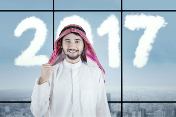Arabian male with numbers 2017 in workplace