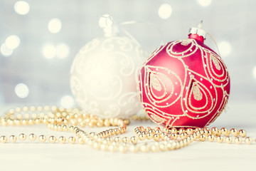 White and red Christmas balls on a holiday lights background