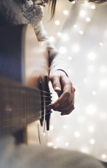 Hipster girl playing guitar in a home atmosphere, person studying on musical instrument on glow bokeh Christmas illumination, female hands using guitar in holiday on relax glitter decoration, blur