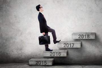 Businessperson walks toward 2017 on stairs