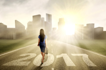 Businesswoman toward city with number 2017