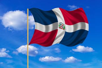 Dominican Republic flag on flagpole wavy, blue sky