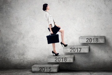 Woman walks toward numbers 2017 on stairs
