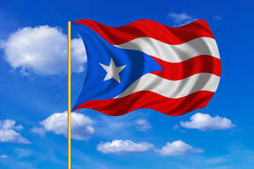 Flag of Puerto Rico waving on blue sky background