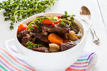 Beef Bourguignon in a white soup bowl. Stew with carrots, onions, mushrooms, bacon, garlic and bouquet garni. The dish is served with fresh thyme.