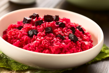 Beetroot risotto prepared with beetroot puree, roasted beetroot pieces on top, photographed with natural light (Selective Focus, Focus on the first beetroot pieces on top of the risotto)