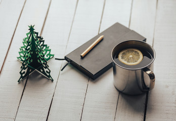 tea cup with lemon, note book, pencil and Christmas decoration.thtranquil mood