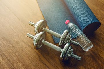 Silhouette Pair of dumbbells with blue yoga mat on wood floor,flare light