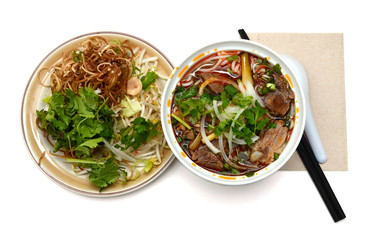 Bun Ho Hue or Vietnamese vermicelli noodles with beef on a white background