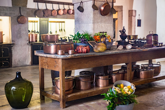 Kitchen of medieval castle copper pans and pots on wall and kitchenware cooking utensils table, Pena Portugal