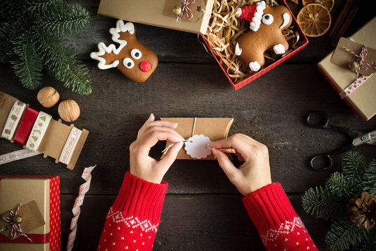Woman wrapping modern Christmas presents with blank gift tag on old wooden background. Eye bird view. Christmas concept.
