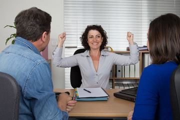 Man and woman with insurance female agent hands up success