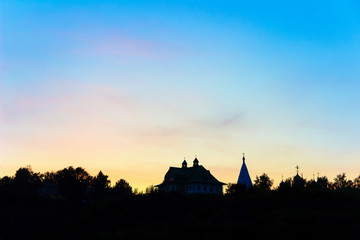 Fototapete - silhouettes of churches at sunset