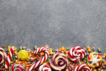 Colorful lollipops, candy canes and sweet candies mix on stone textured background