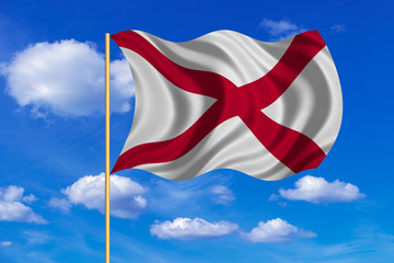 Flag of Alabama waving on blue sky background
