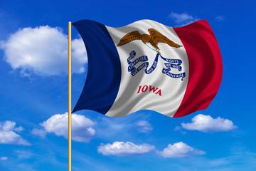 Flag of Iowa waving on blue sky background