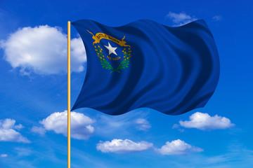 Flag of Nevada waving on blue sky background