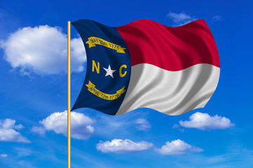Flag of North Carolina waving on blue sky backdrop