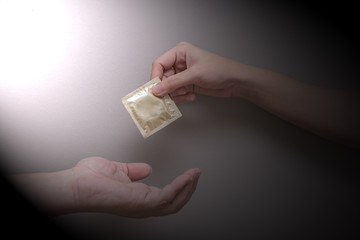 Woman's hand giving man's hand a gold condom in a black-grey gradient background, safe sex concept