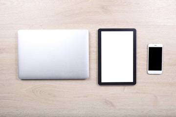 Laptop computer with mockup tablet and smartphone devices on woo