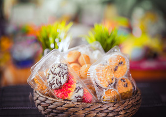 Plastic disposable containers with cookies and pastries in a wicker wooden basket on a motley, colored background