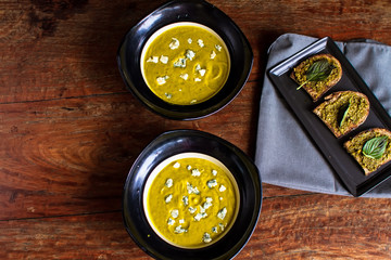 Pumpkin kozy cheese and spinach cream soup, bread with pesto sauce and basil.Pumpkin and carrot soup with cream and parsley on dark wooden background