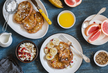 Breakfast - caramel french toast with banana, cottage cheese with granola and pomegranate, fresh grapefruit on a blue background. Top view, flat lay