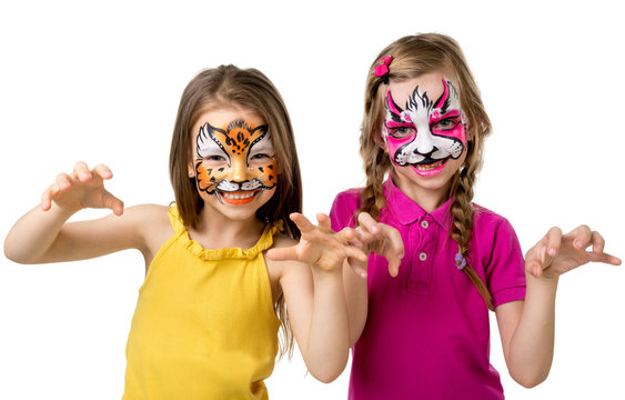 two little girls with painted faces growling like animals