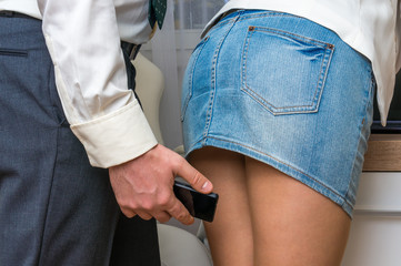 Man taking photo with mobile phone of woman's butt