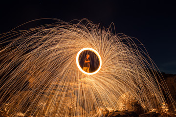 Showers of hot glowing sparks from spinning steel wool on the rock