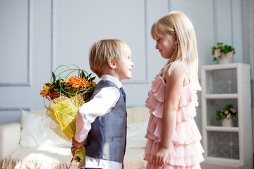 Boy is presented flowers to girl. Studio shot